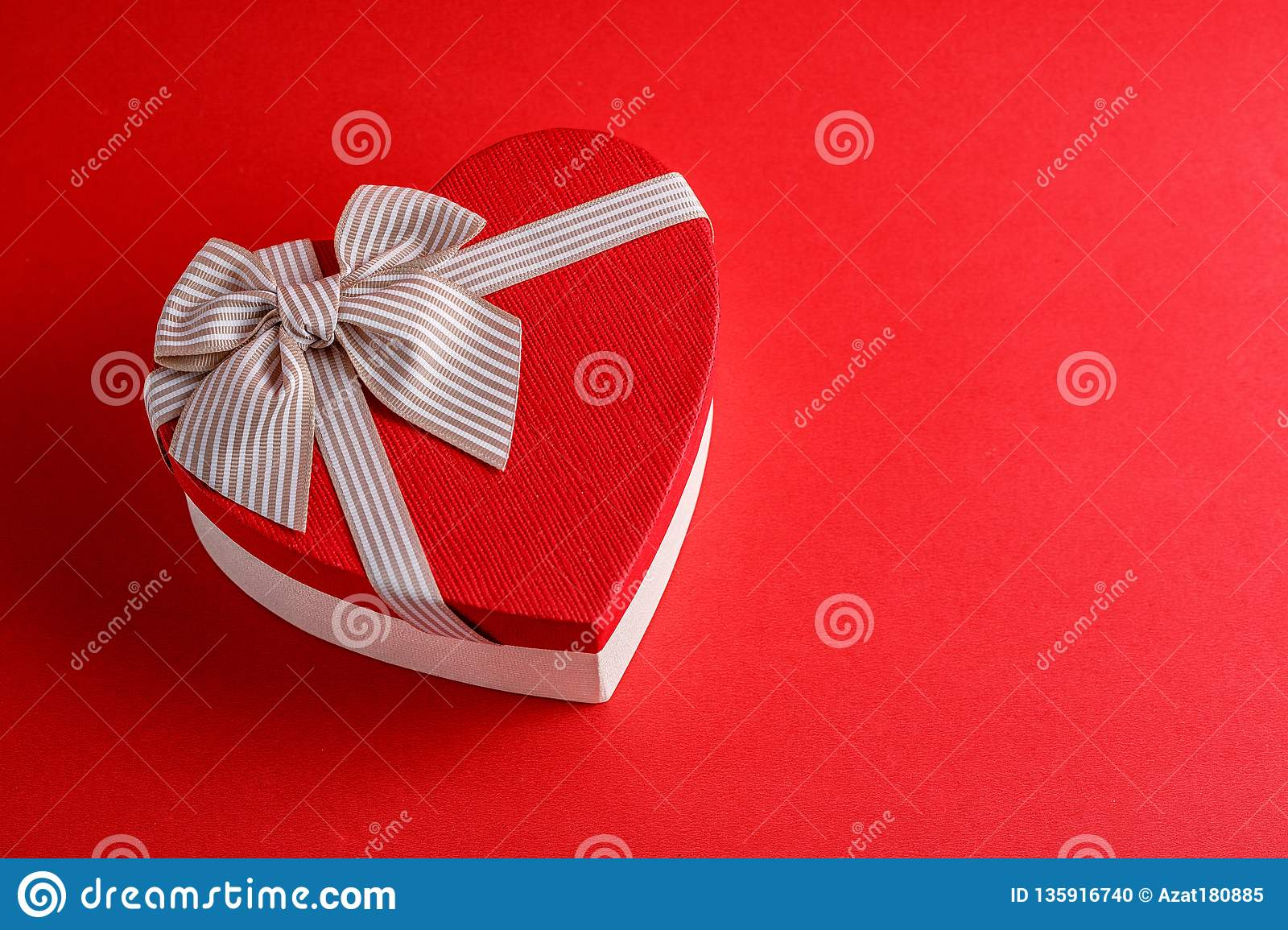 Gift box in the shape of a heart with a ribbon on a red background. The concept is suitable for love stories, birthdays and Valent