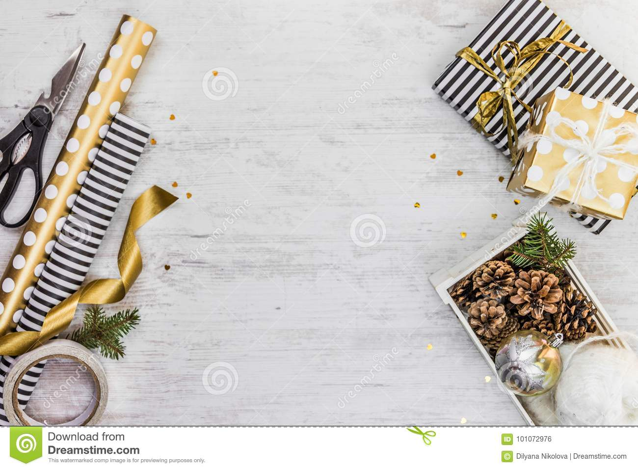 Gift box wrapped in black and white striped paper with golden ribbon, a crate full of pine cones and christmas toys and wrapping m