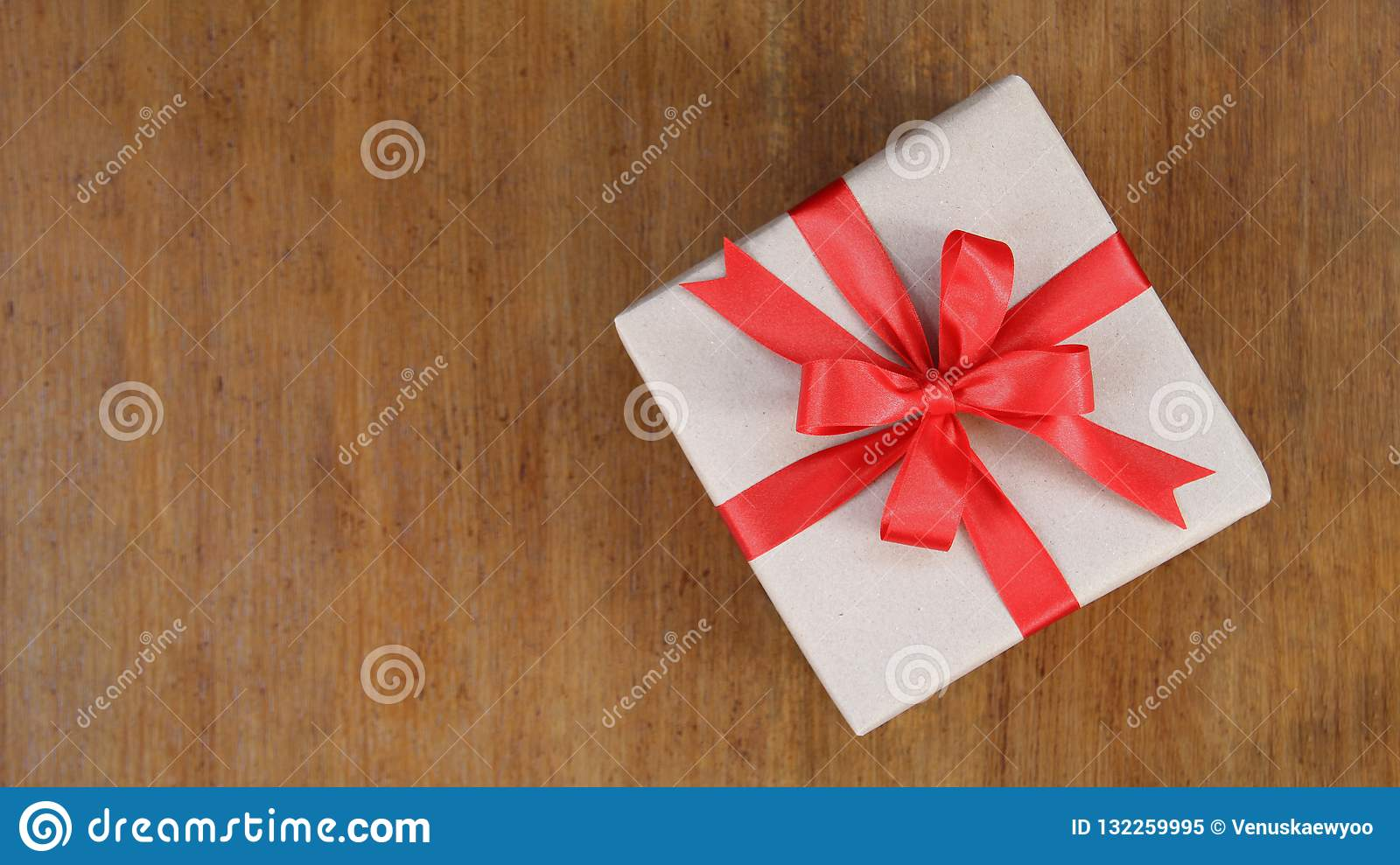 Gift box wrapped in brown recycled paper with red ribbon bow top
