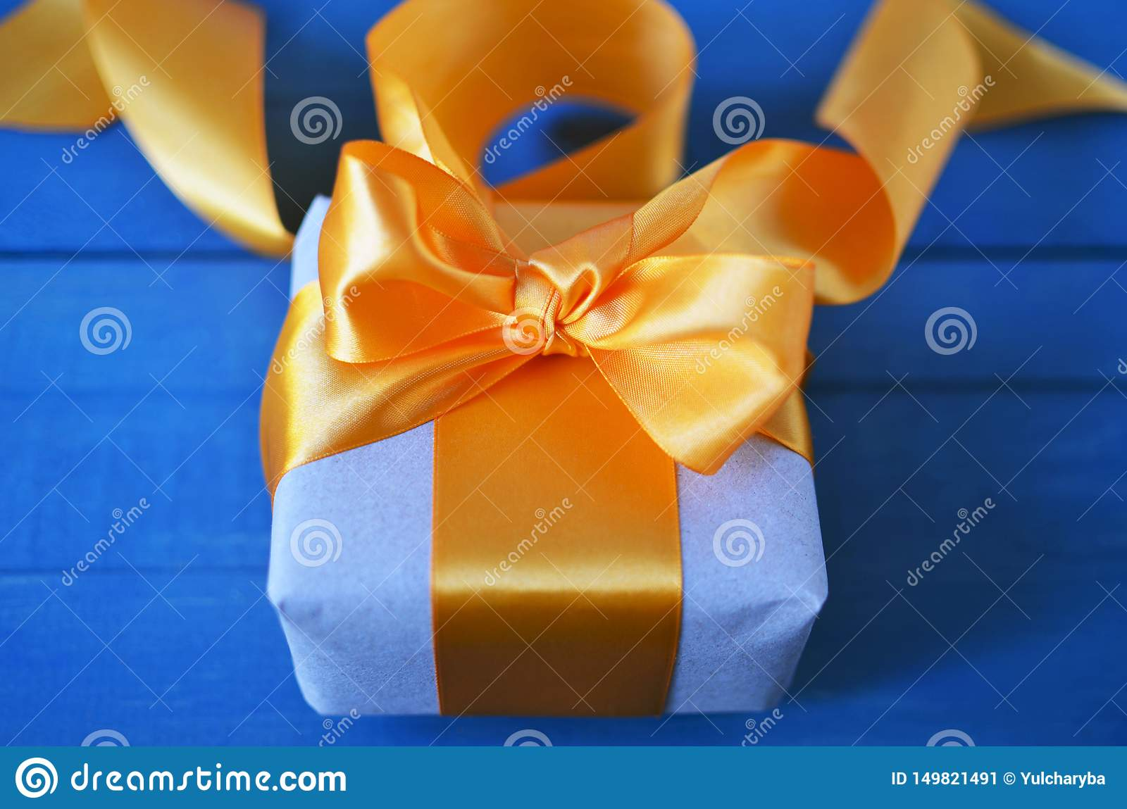 Gift box wrapped with craft paper and bow on neutral background with boke. Holiday concept.