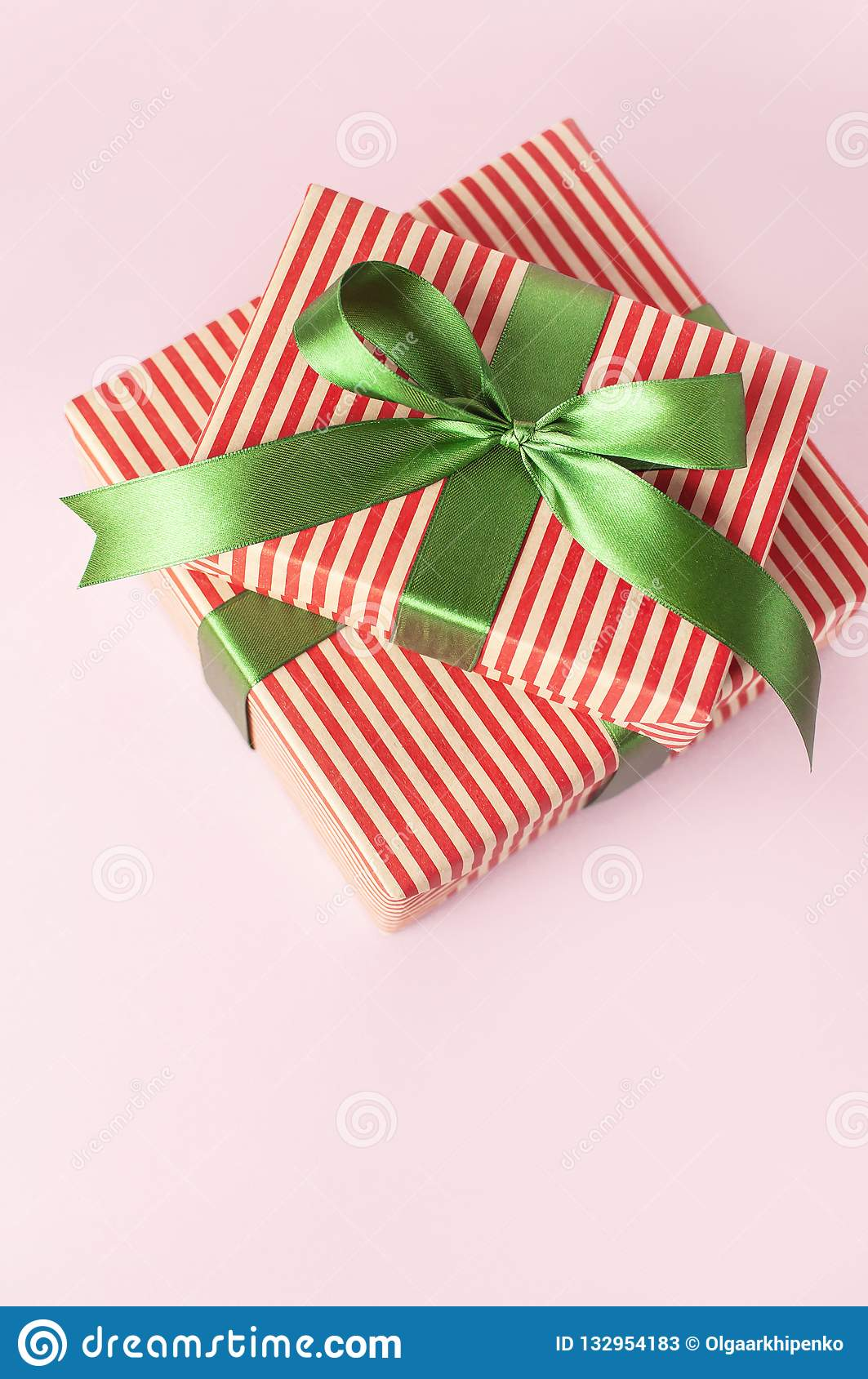 Gift boxes with green ribbon on pink background top view flat lay. Holiday concept, new year or Christmas gift box, presents Xmas