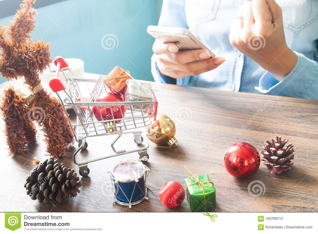 gift boxes in shopping cart and christmas decorations on table woman using mobile device online shopping concept - Christmas Decorations Online