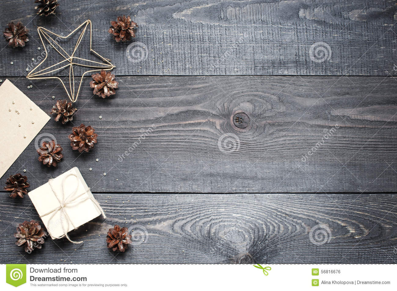Gift, card, pine cones and cinnamonin on the dark wooden texture