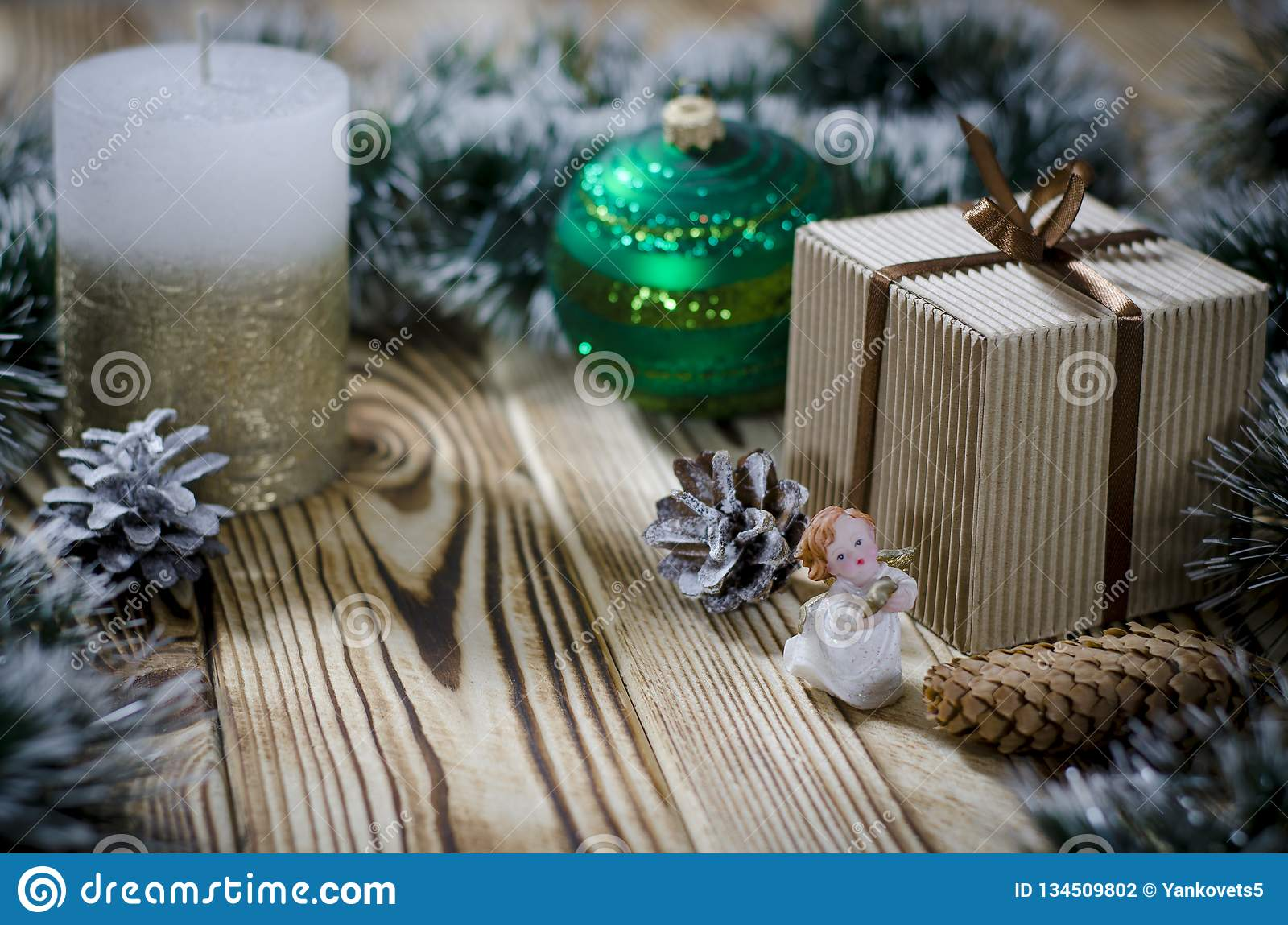 A gift lays on a wooden table next to a candle, cones and an angel against the background of Christmas decorations
