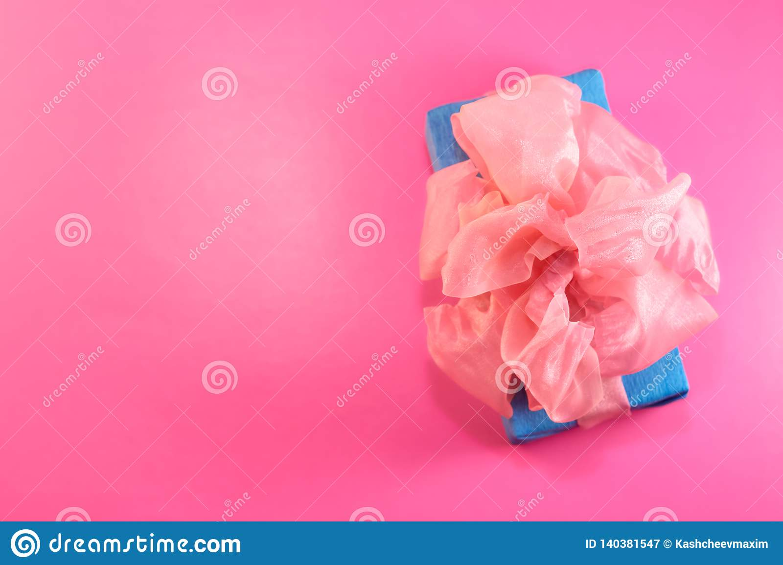 The gift is packed and decorated with a pink bow on a pink background with copy space. Flat lay, top view. copy space