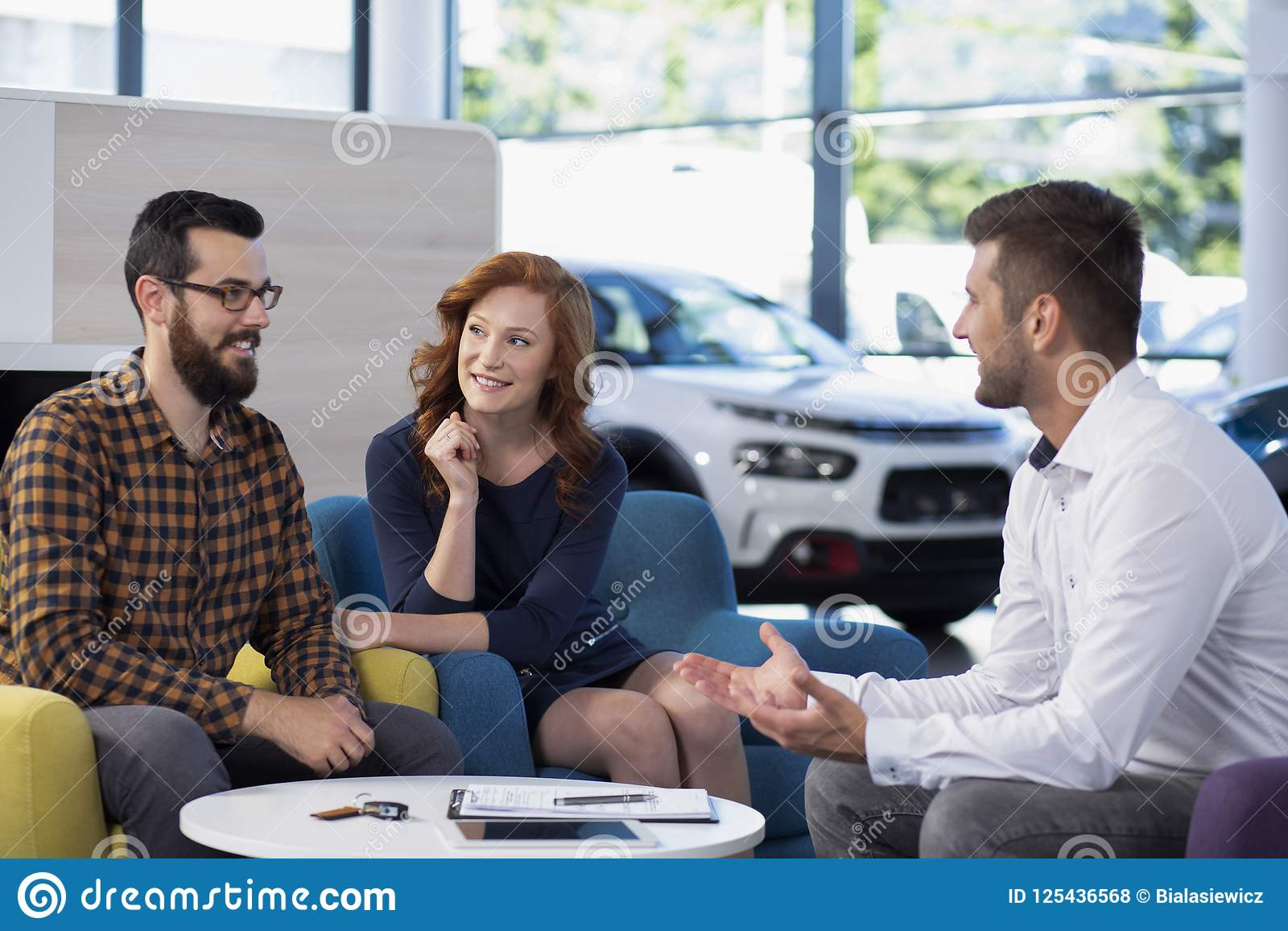 Gift par som talar till en bilåterförsäljare i en visningslokal