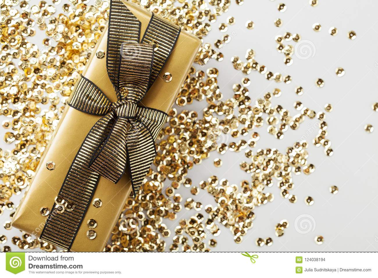 Gift Or Present Box Packed In Golden Paper And Sequins On Table Top