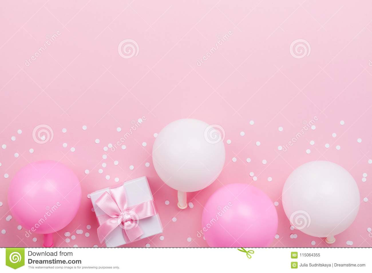 Gift or present box, pastel balloons and confetti on pink table top view. Flat lay composition for birthday, mother day or wedding