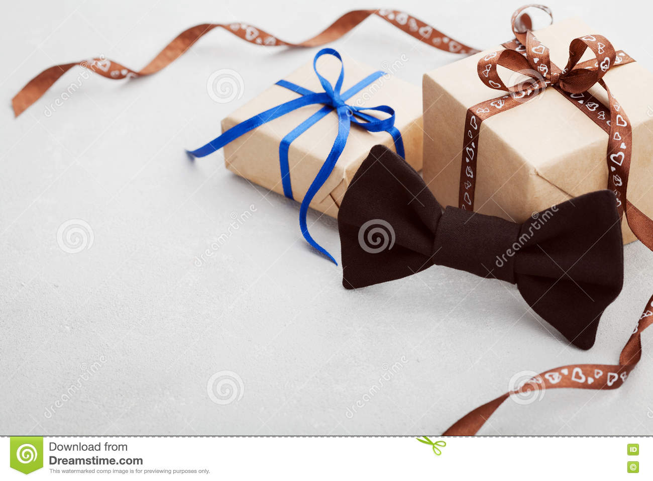 Gift or present box with ribbon and bowtie on gray desk for Happy Fathers Day, copy space for your text or design