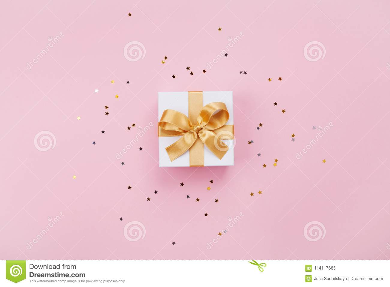 Gift or present box and stars confetti on pink pastel table top view. Flat lay composition for birthday, mother day or wedding.