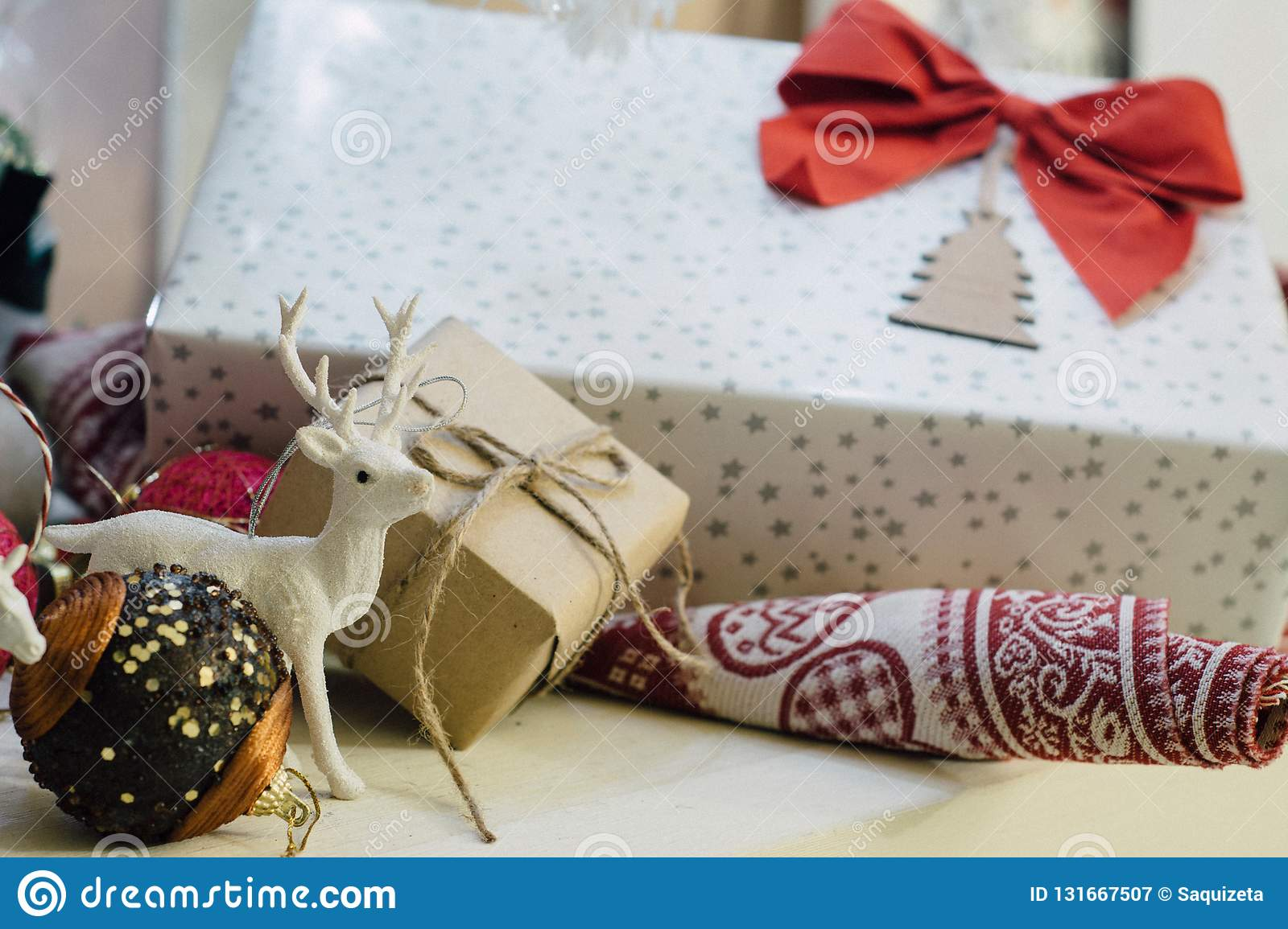Gift With Red Bow Next To The White Christmas Tree, Shot Of Ornaments Stock Image - Image of ...