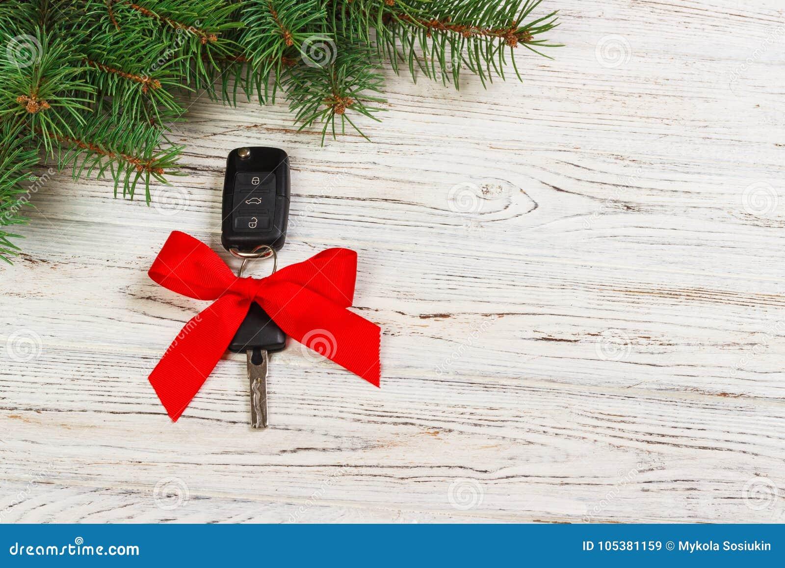 Gift voor de sleutels van de Kerstmisauto Close-upmening van autosleutels met rode boog zoals huidig op houten achtergrond