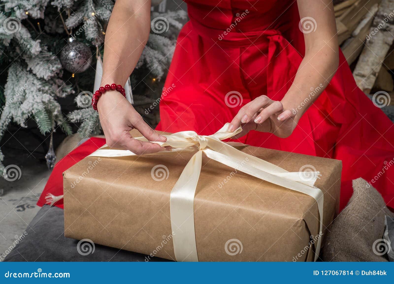 Gift voor Kerstmis: Een meisje in een rode kleding pakt een doos met een gift in en verbindt het lint