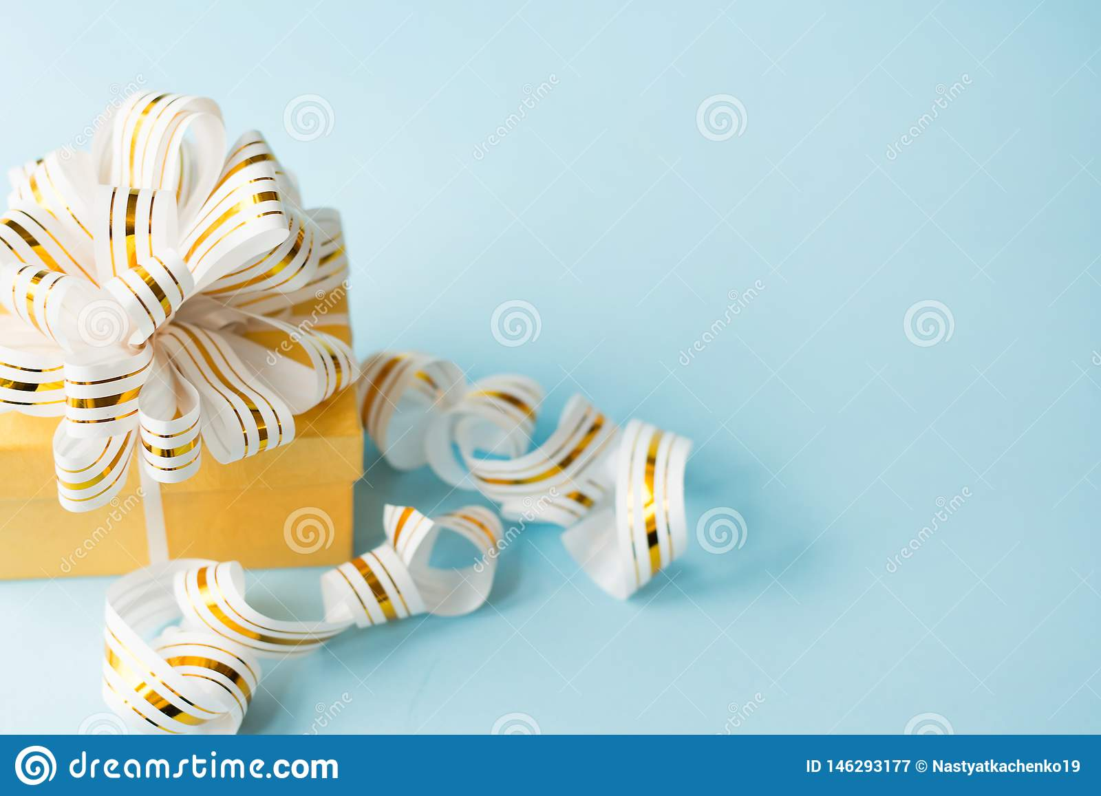 Gift wrapped with bow on blue background with copy space . flat lay greeting card