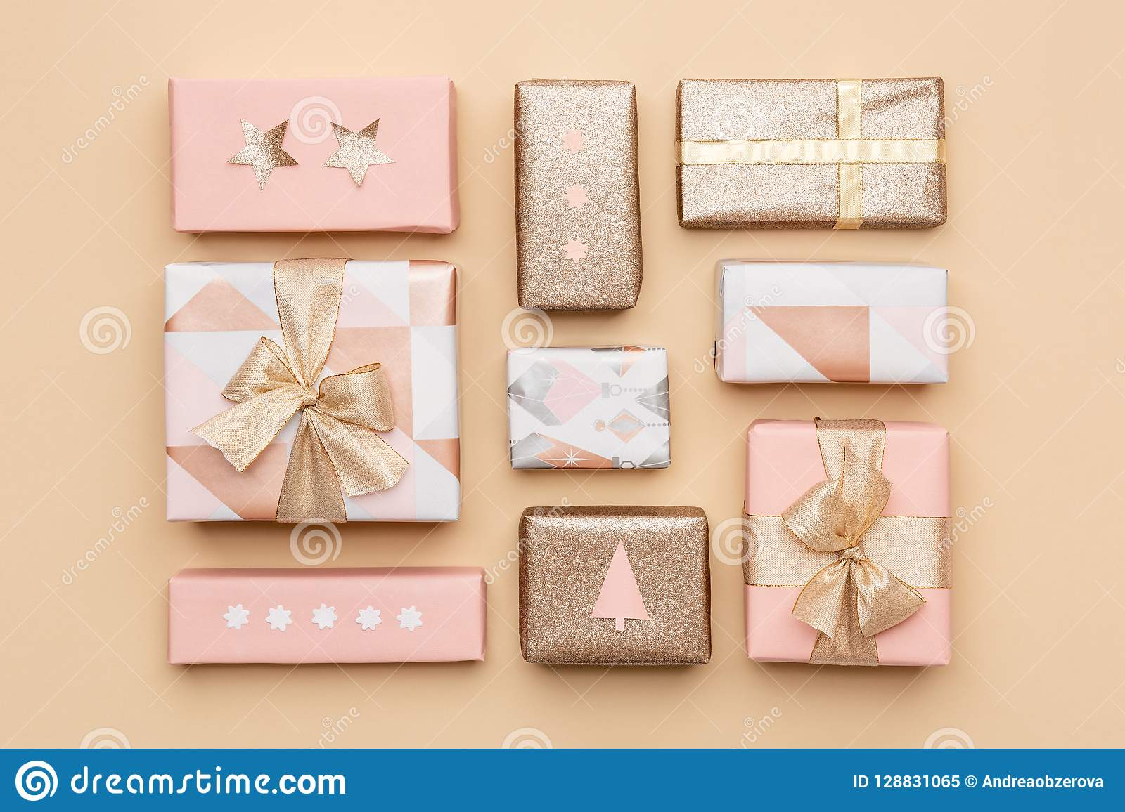 Gift wrapping composition. Beautiful nordic christmas gifts isolated on gold background. Pink and gold colored wrapped gift boxes.