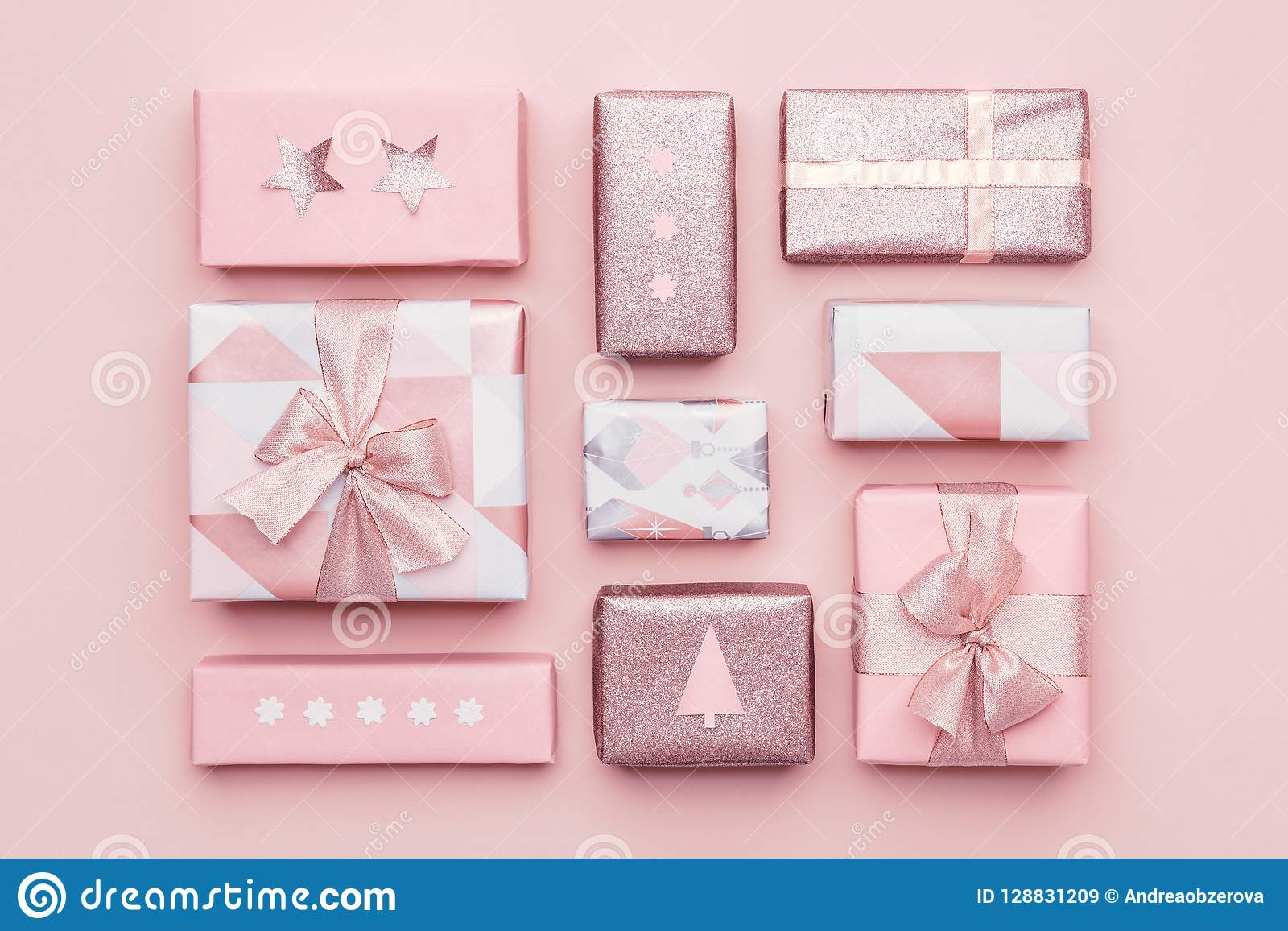 Gift wrapping composition. Beautiful nordic christmas gifts isolated on pastel pink background. Pink colored wrapped gift boxes.