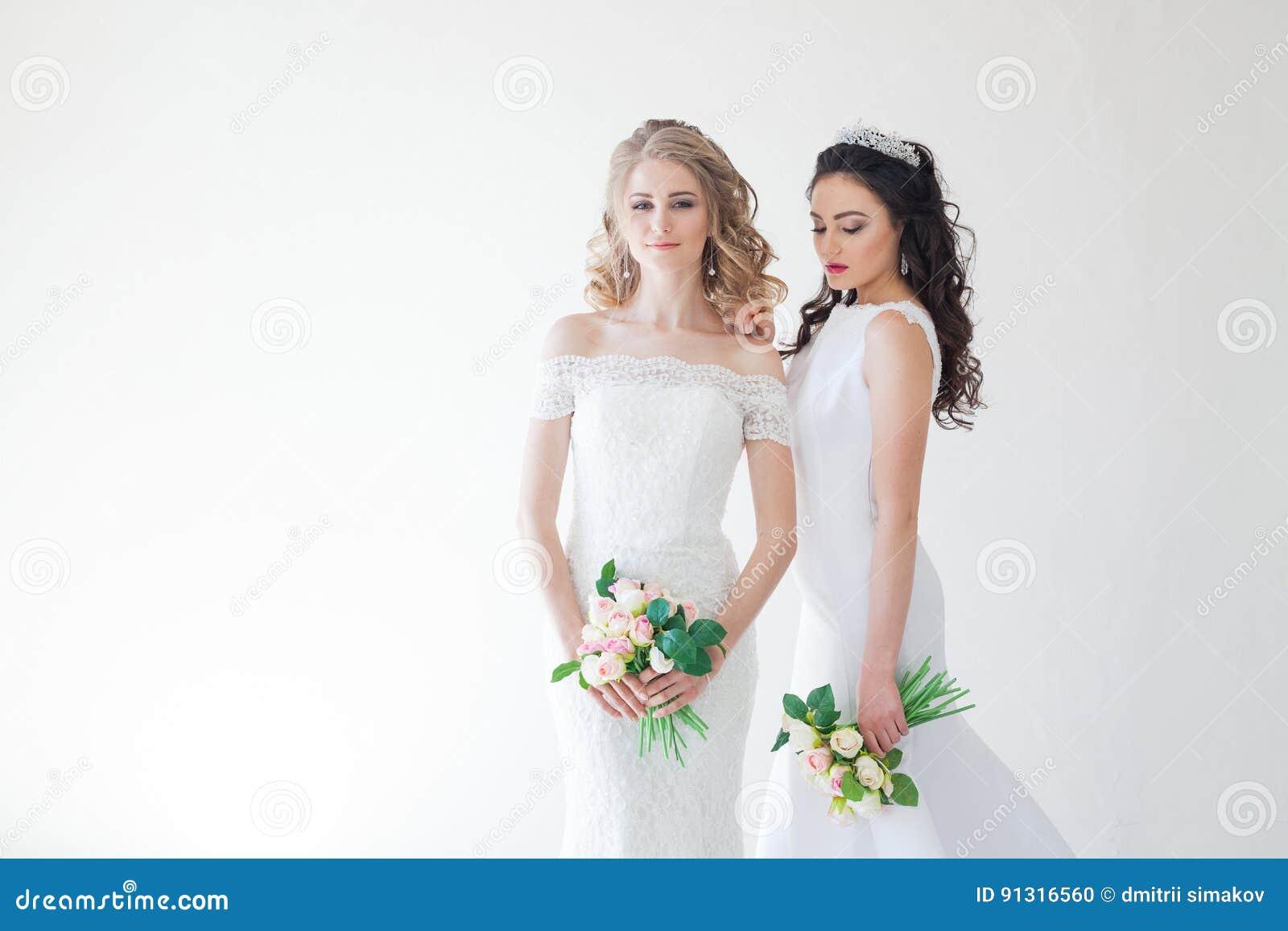Gifta sig brud två med en bukett av blommor som gifta sig hår