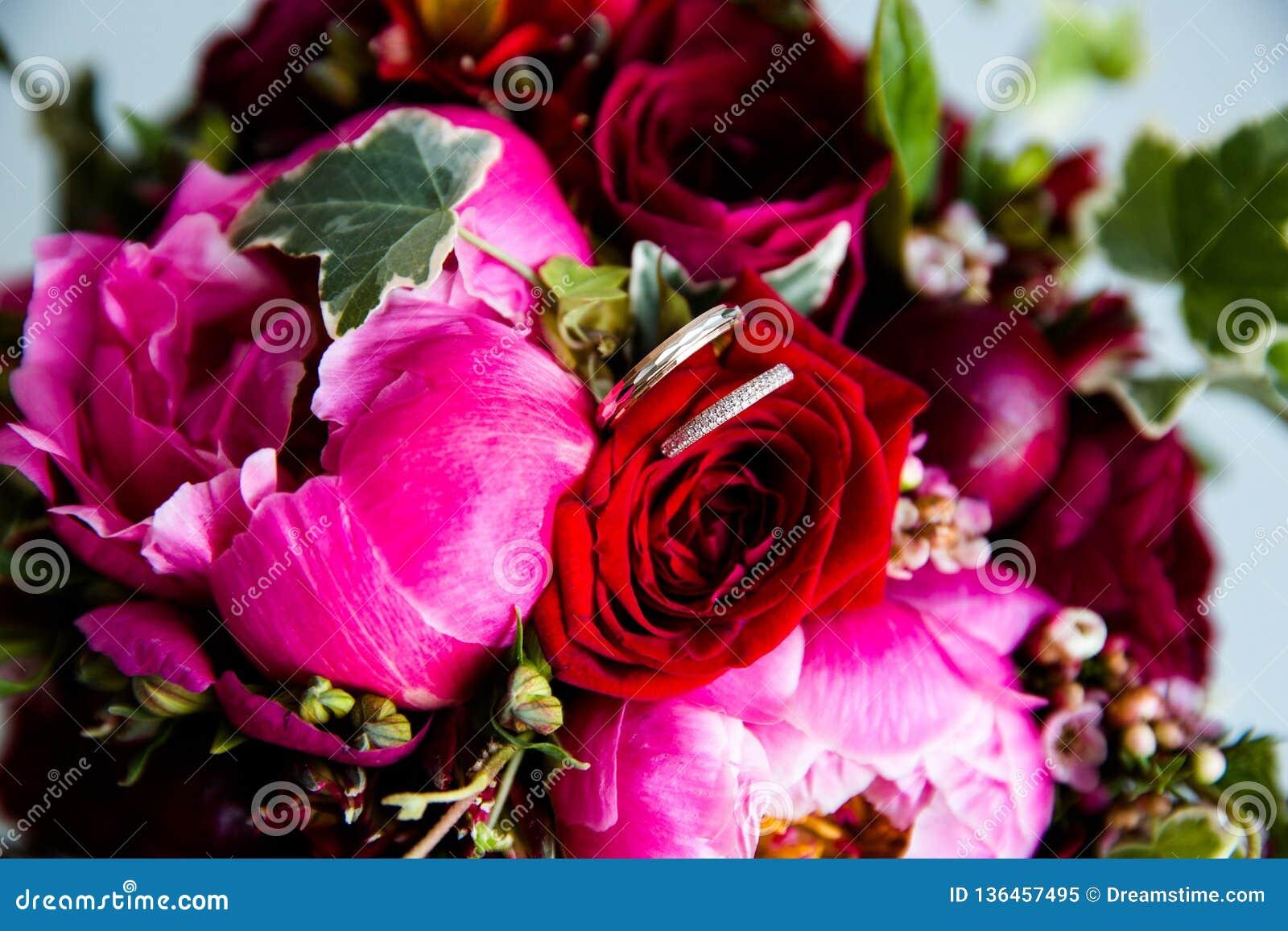 Gifta sig guld- cirklar på en bukett av blommor