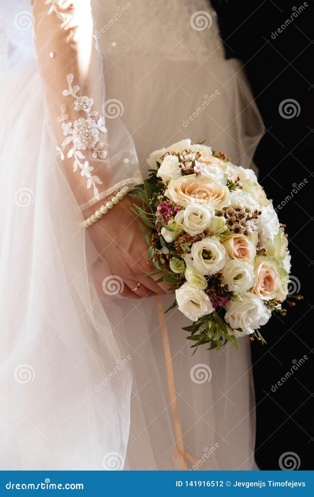 Gifta sig modeståenden av unga par med trevlig boquet Brud och brudgum i Riga, Lettland