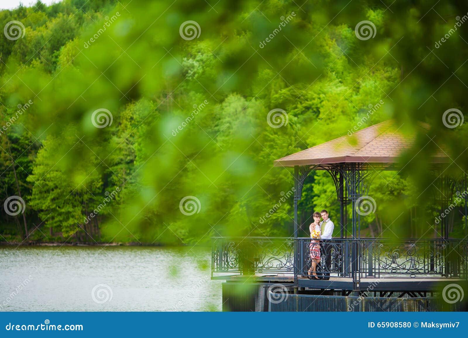 Gifta sig nyligen par som omfamnar bredvid en sjö