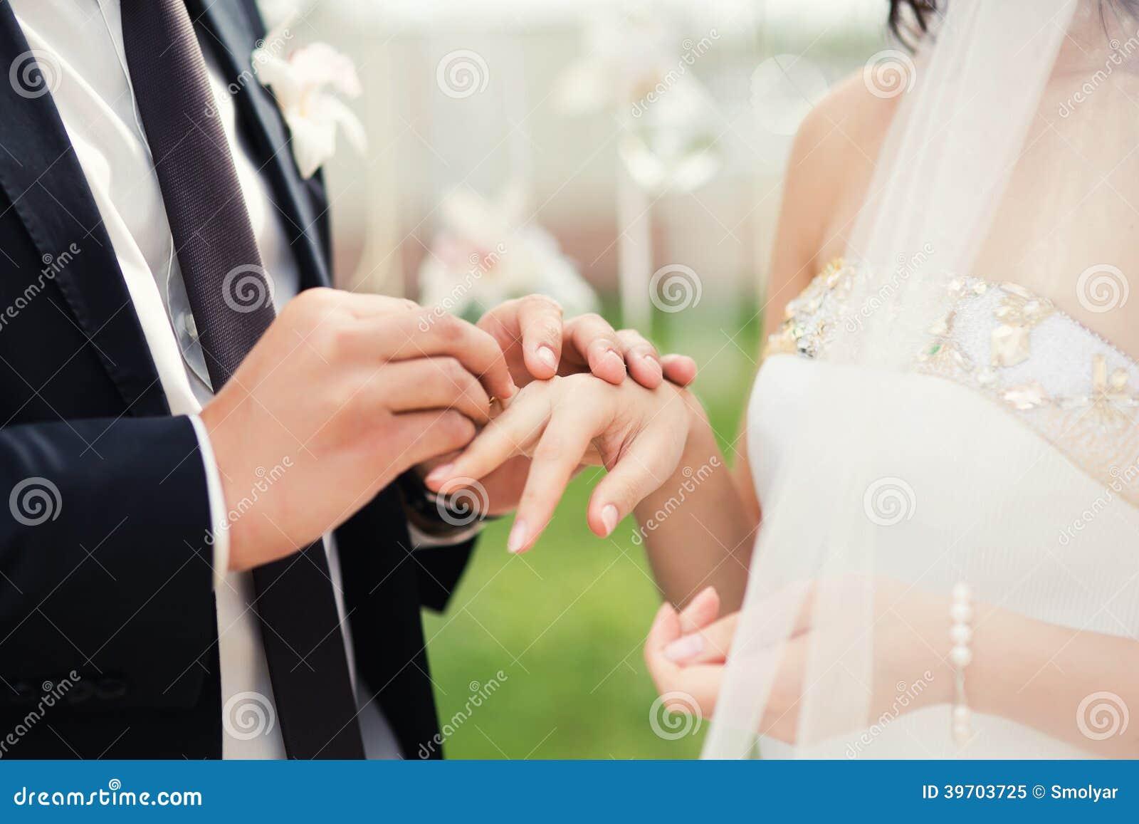Gifta sig par räcker närbild under bröllopceremoni