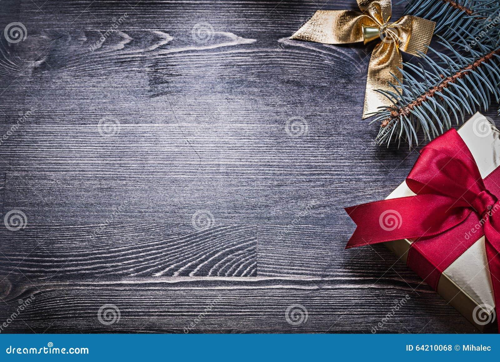 Giftbox de la rama del pino del arco de la Navidad en el tablero de madera