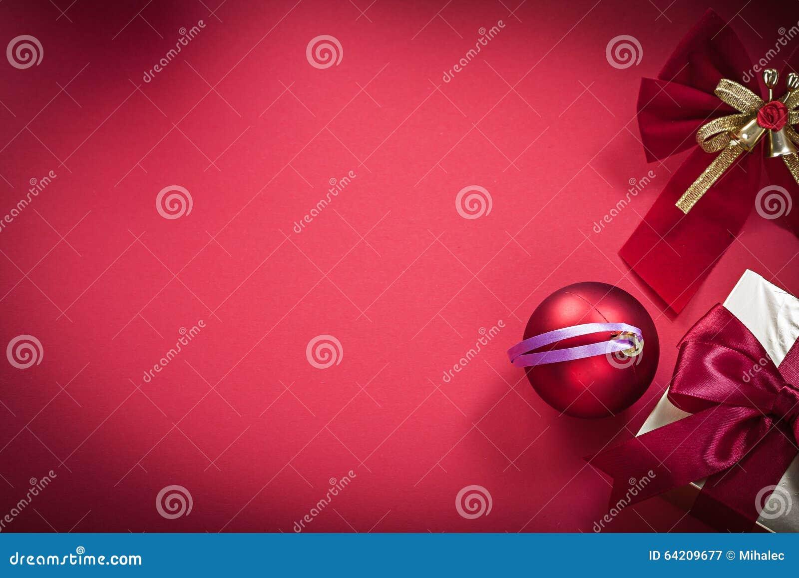 Giftbox del arco de la bola de la Navidad en fondo rojo