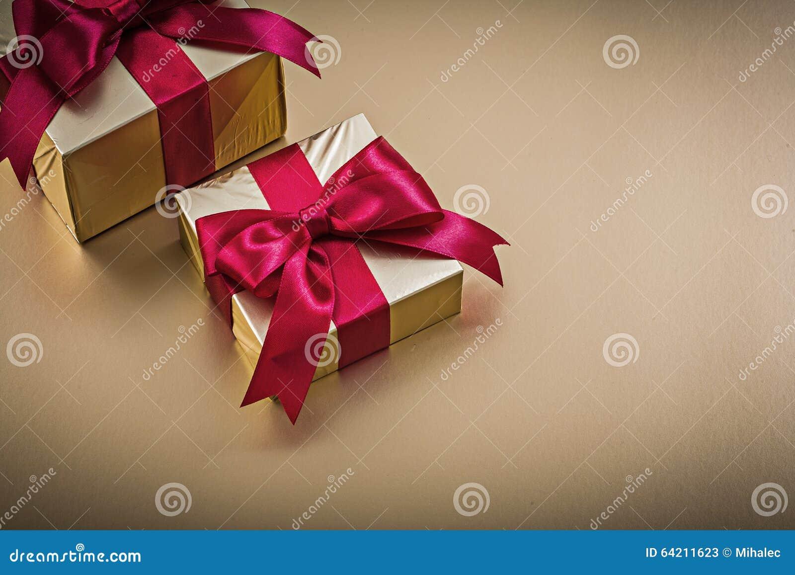 Giftboxes envueltos con los arcos atados en superficie de oro