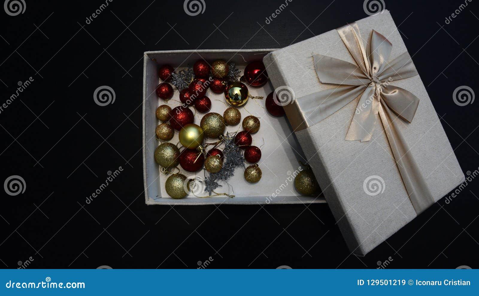 Giftdoos met Kerstmisbollen binnen tegen donkere achtergrond