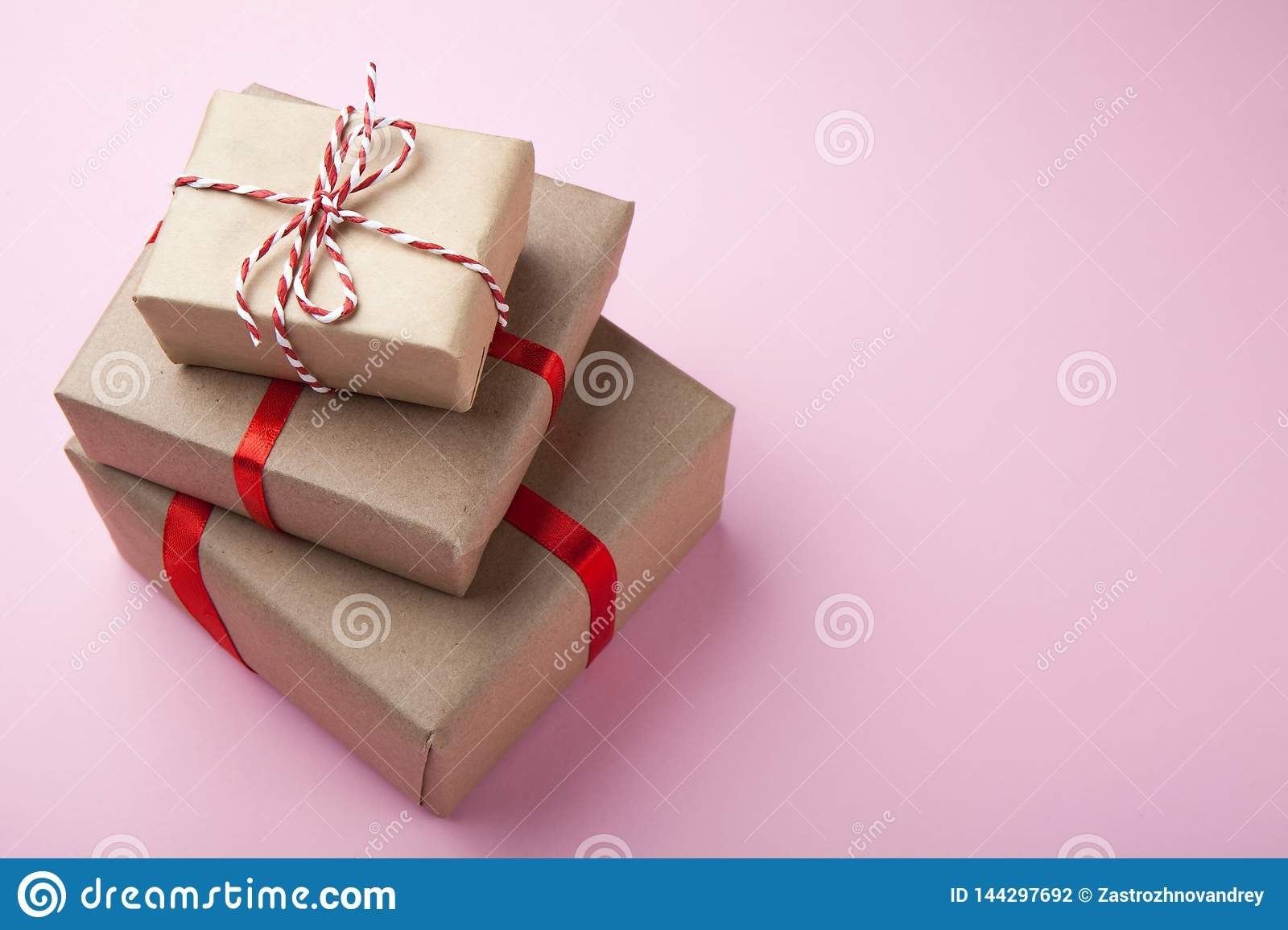 Gifts in a beautiful and elegant package on a pink background. View from above
