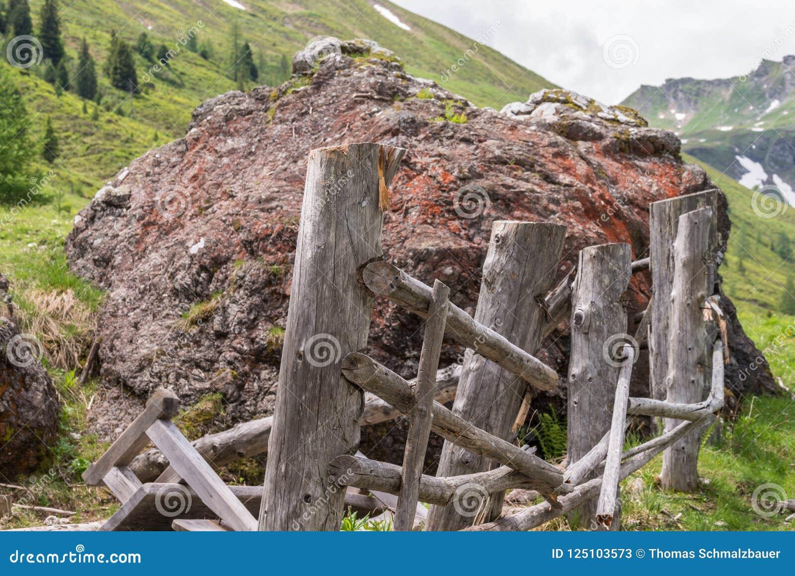 Giganta kamienny głaz na paśniku niszczącym drewnianym ogrodzeniu i, Austria