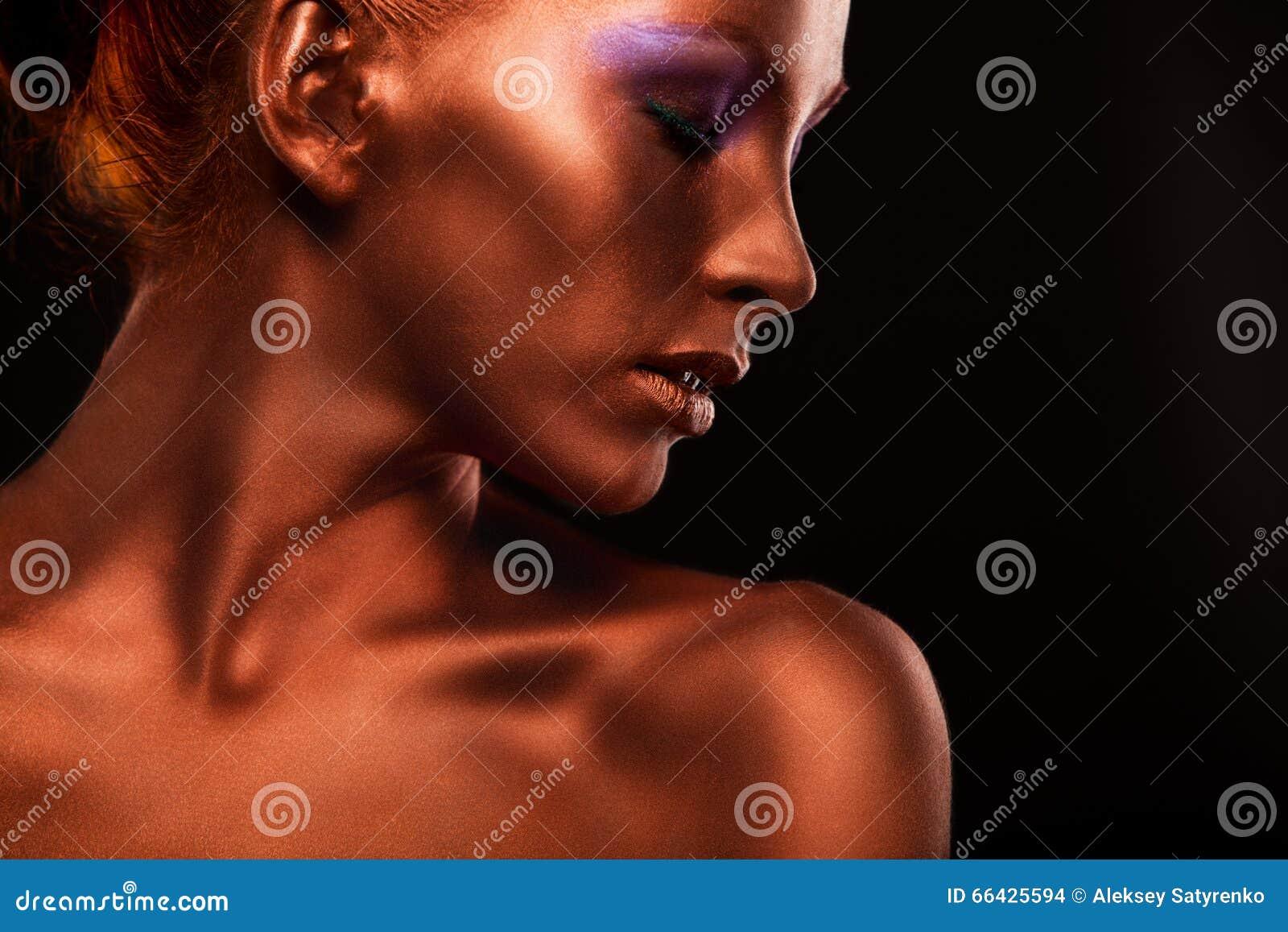 Gilt Guld- kvinnas framsidaCloseup Futuristiskt förgyllt smink Målad hudbrons