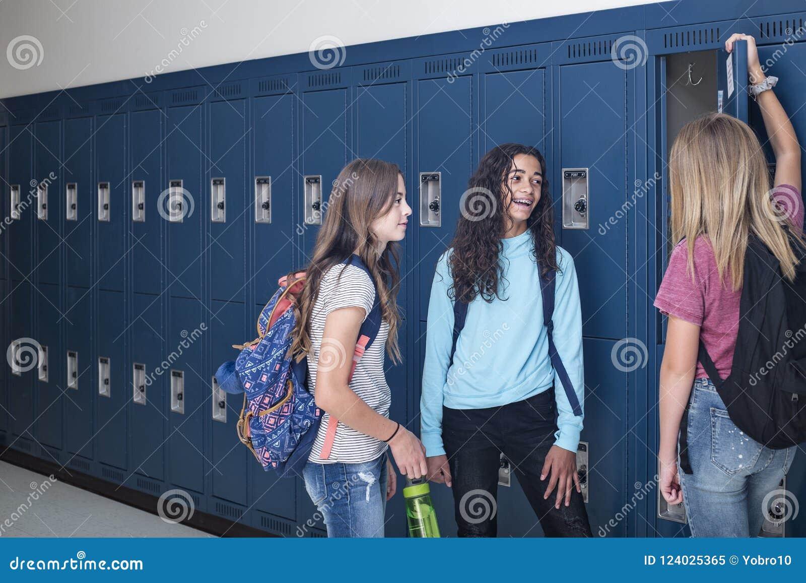 Gimnazjum ucznie opowiada i stoi ich szafką w szkolnym korytarzu