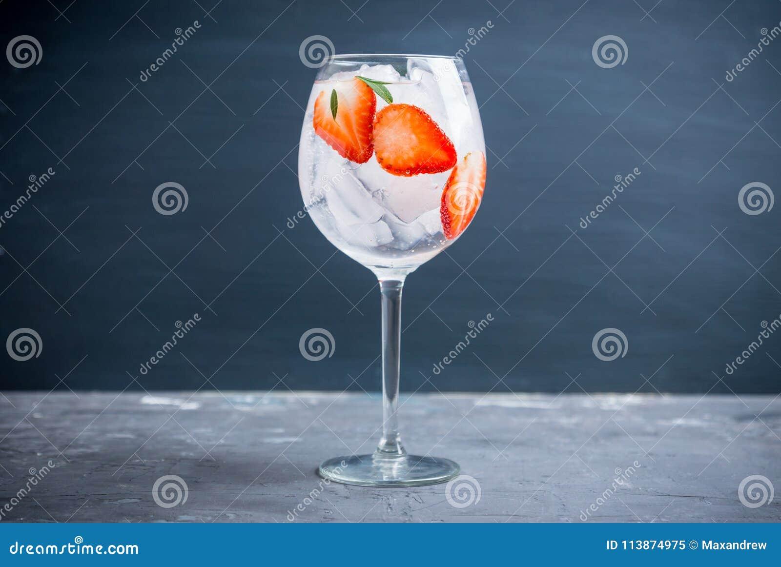 Gin con la fragola ed il ghiaccio in vetro di vino