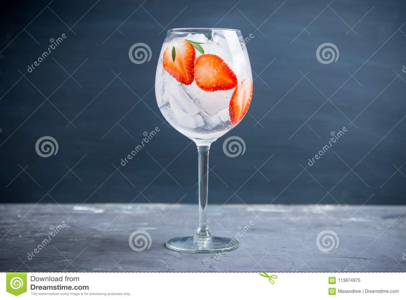 Gin with strawberry and ice in wine glass