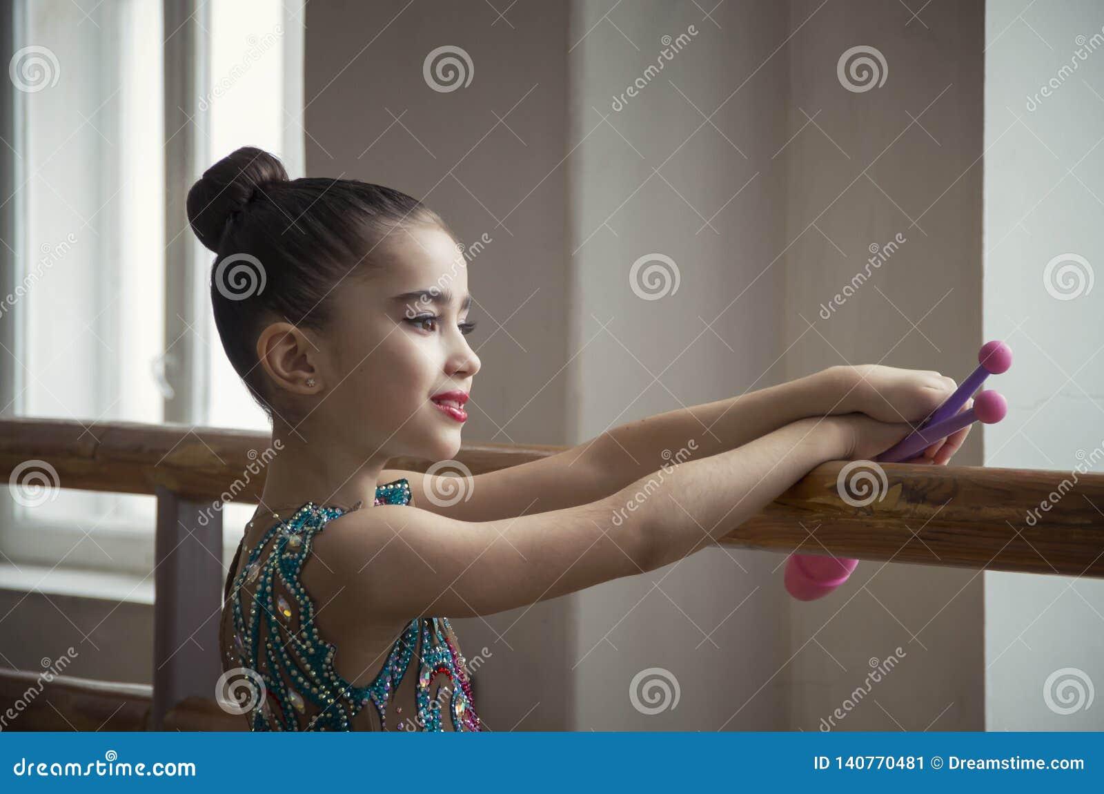 A ginasta da moça com clubes olha através de uma grande janela no salão para o horeography