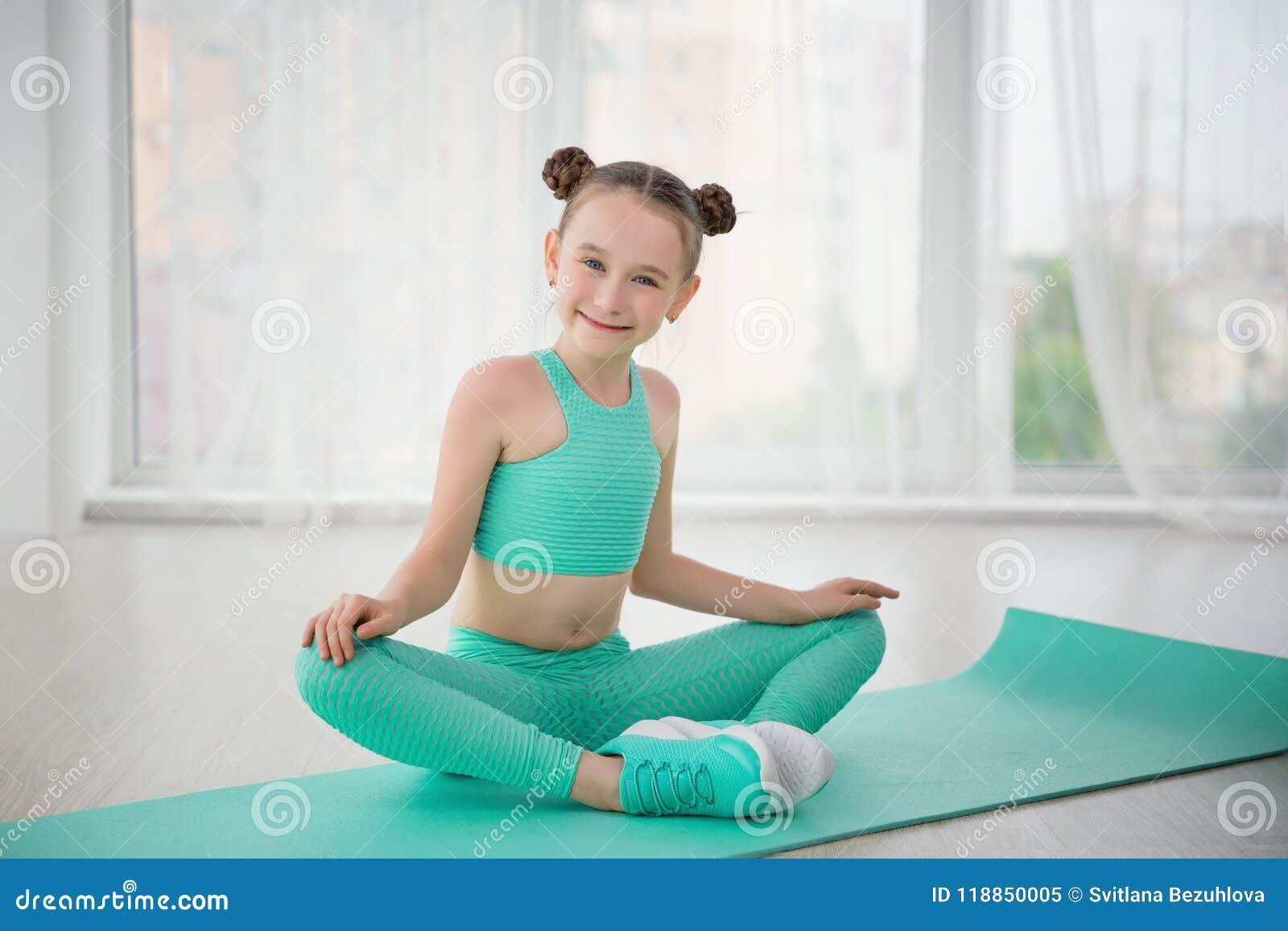 Ginasta desportiva pequena da menina no sportswear que faz exercícios em uma esteira interna