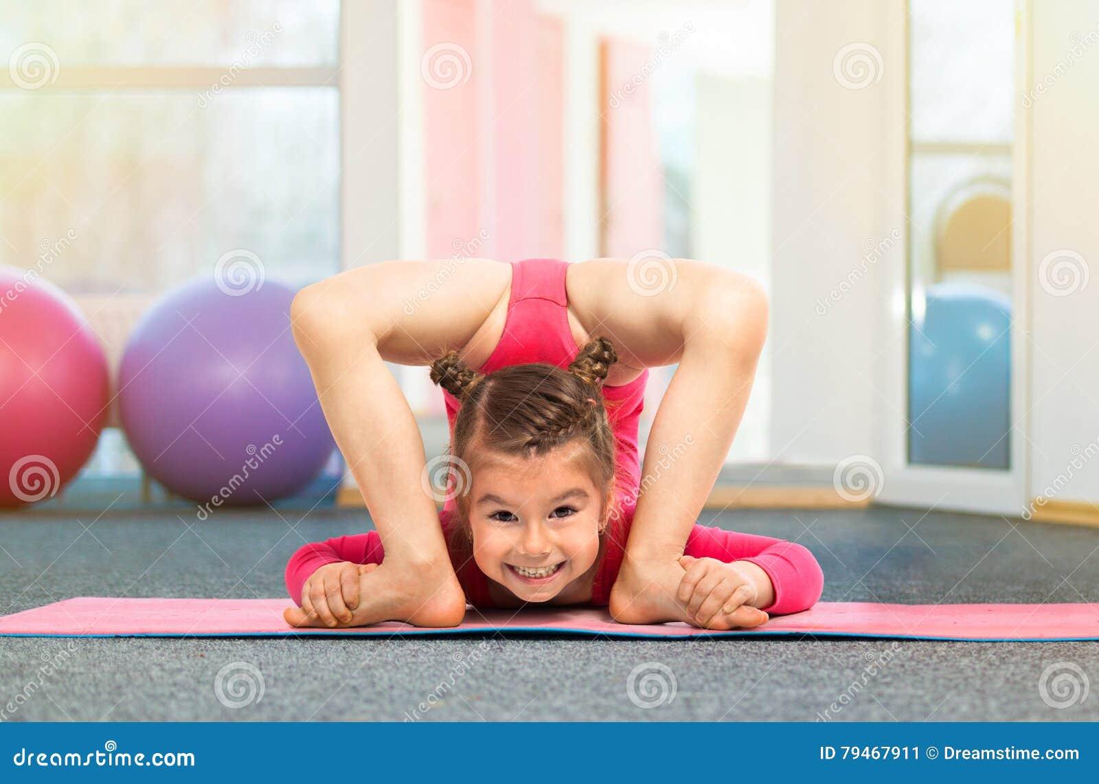 Ginasta flexível da menina que faz o exercício acrobático no gym