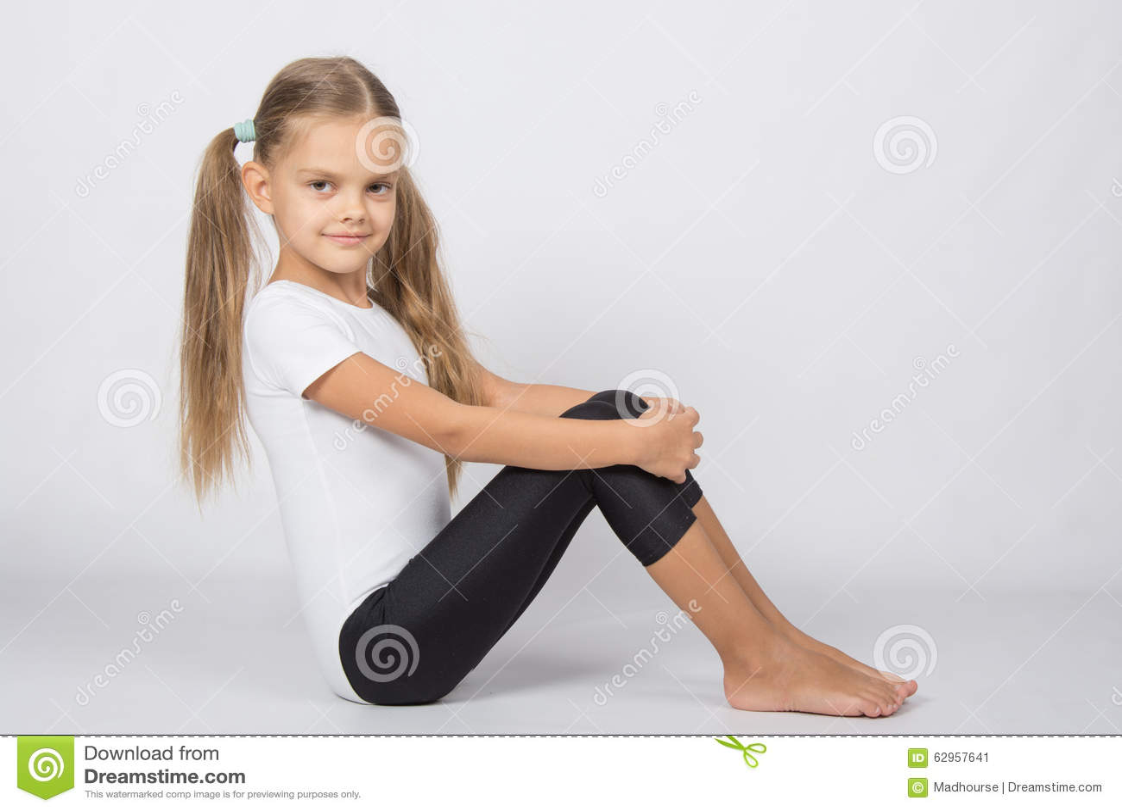 Ginasta seis anos que sentam-se abraçando seus pés dos joelhos