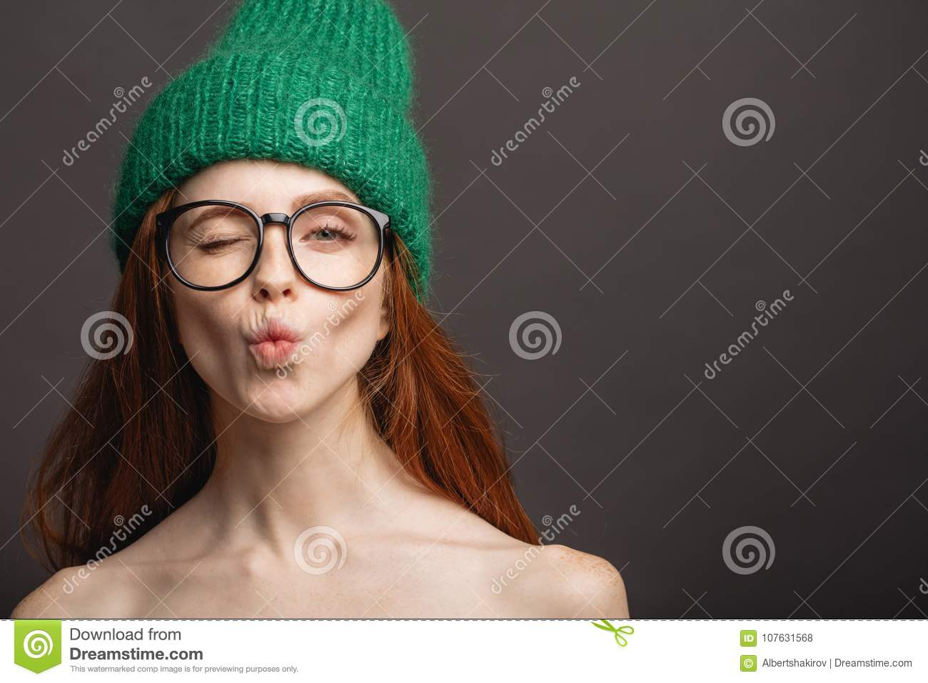 9342f0c17891a Ginger woman wearing glasses and green hat pouting her lips ready for kiss