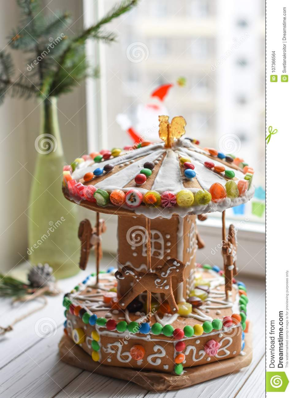a gingerbread carousel and some christmas decoration elements on a white wooden surface