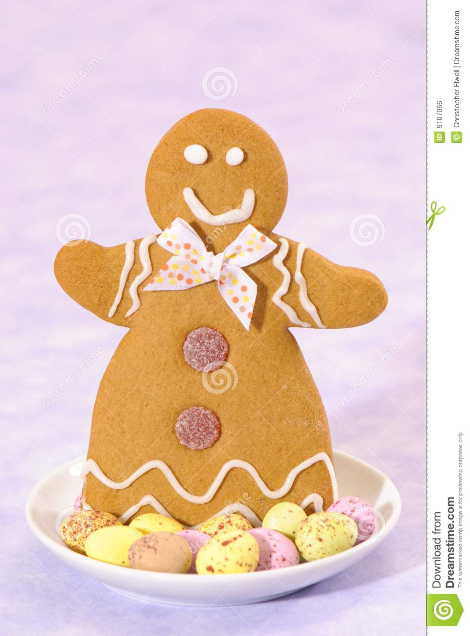 Gingerbread lady in a dish of speckled chocolate eggs on a lilac ...