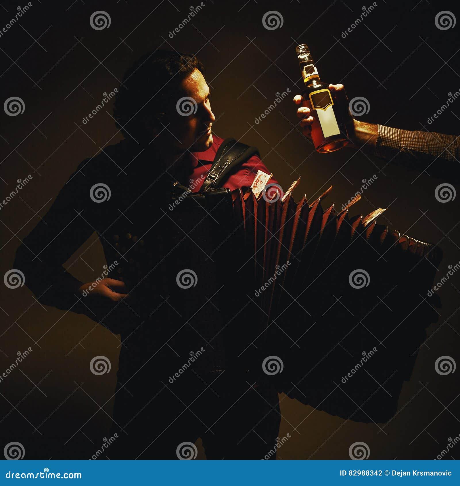 Giocatore della fisarmonica e bottiglia cromatici della bevanda di spirito