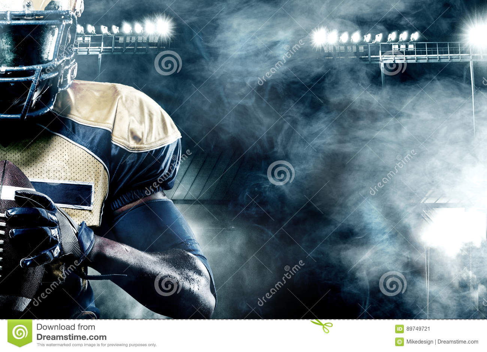 Giocatore dello sportivo di football americano sullo stadio con le luci su fondo con lo spazio della copia