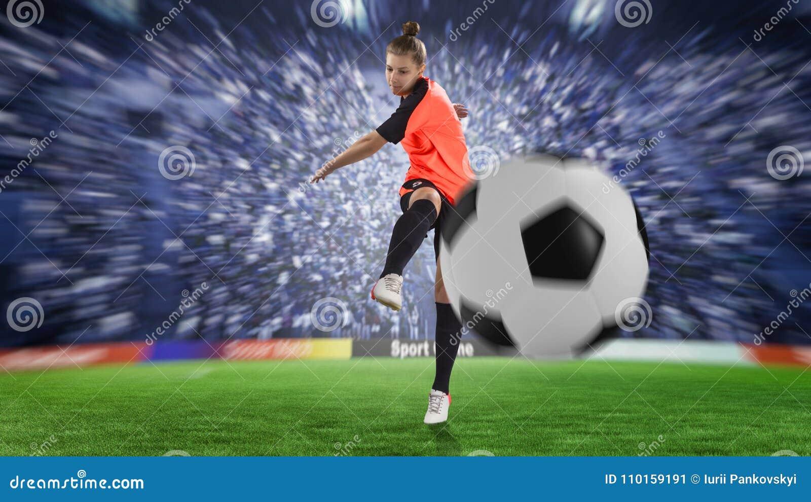 Giocatore di football americano femminile in uniforme dell arancia che dà dei calci alla palla