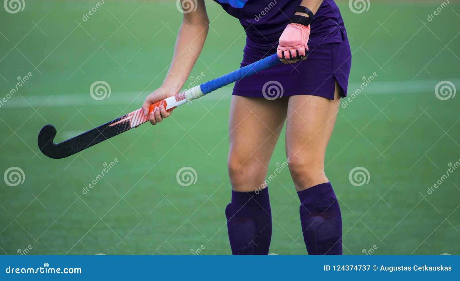 Giocatore di hockey su prato, in possesso della palla, investendo un passo del astroturf, cercante un compagno del gruppo per pas