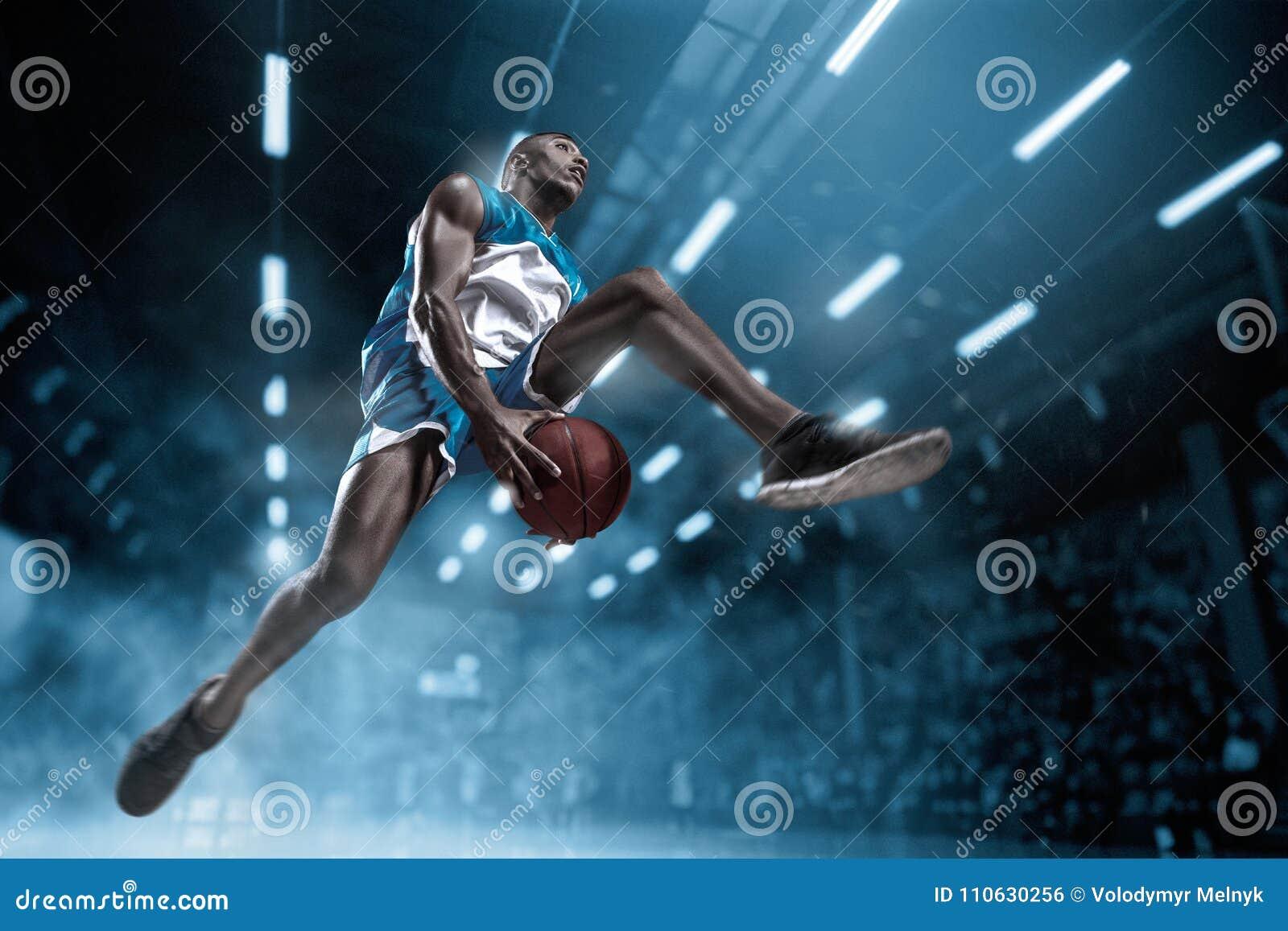 Giocatore di pallacanestro sulla grande arena professionale durante il gioco Giocatore di pallacanestro che fa schiacciata
