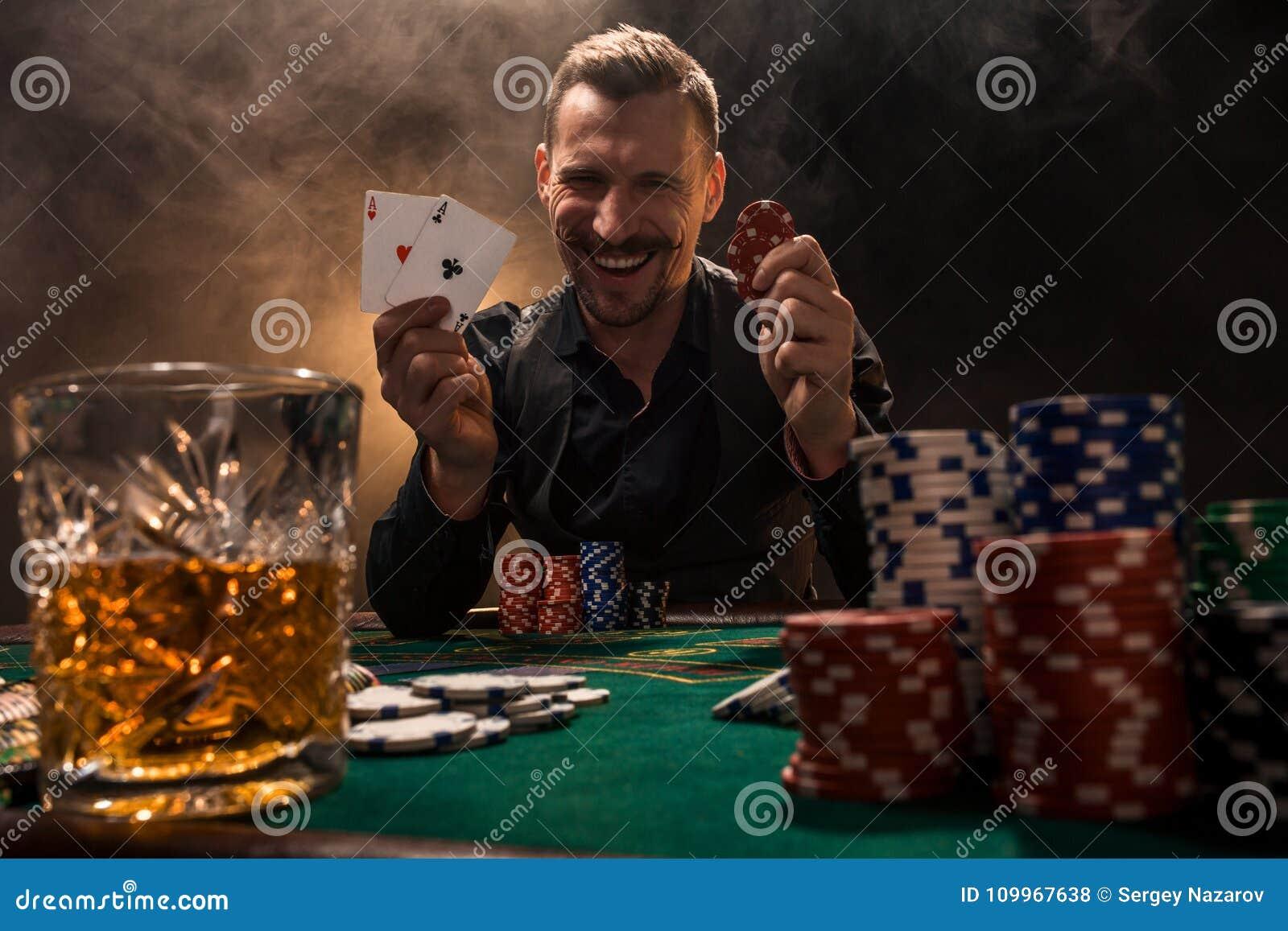 Giocatore di poker bello con due assi nelle suoi mani e chip che si siedono alla tavola del poker in una stanza scura in pieno de