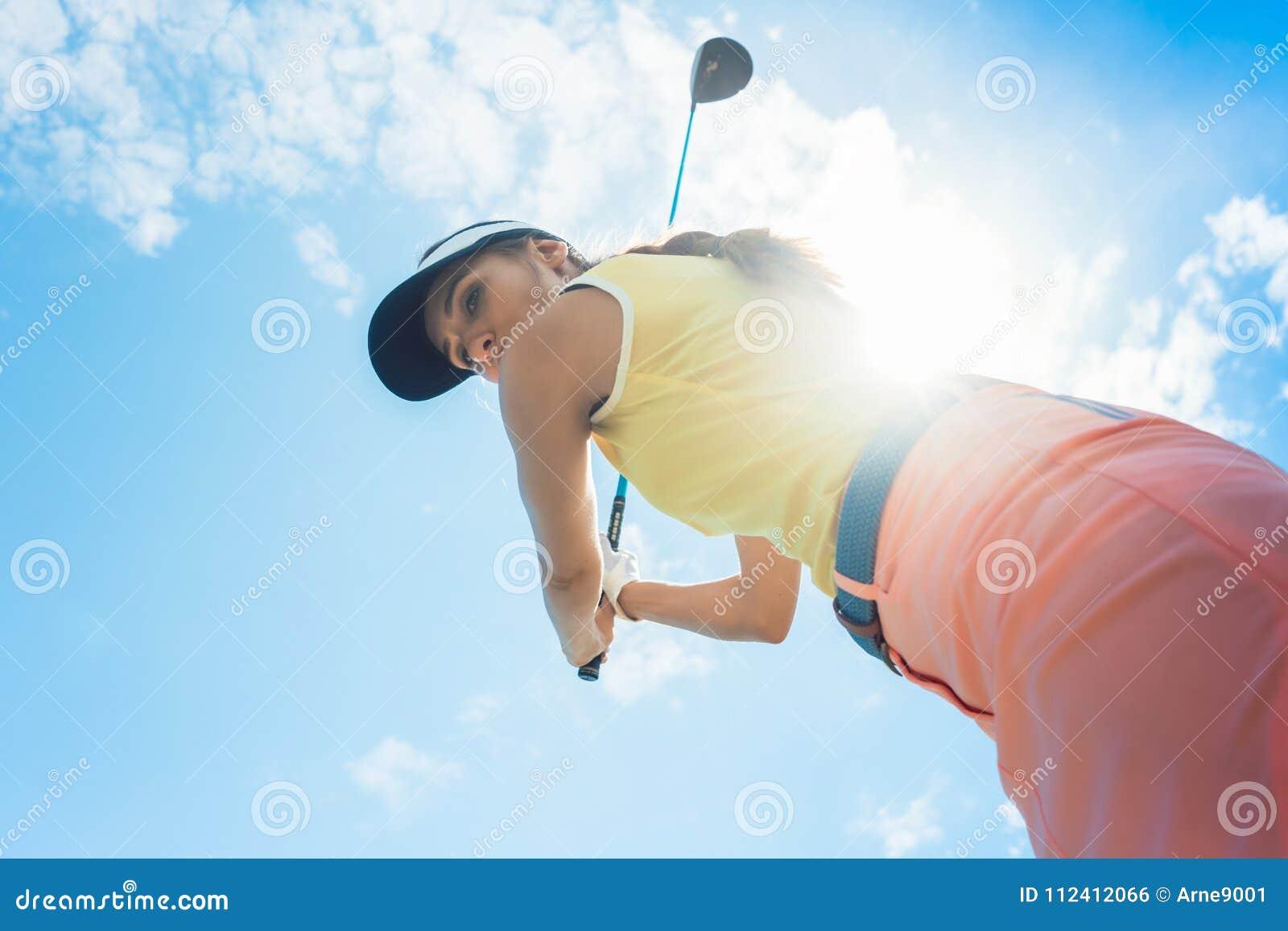 Giocatore professionale femminile che sostiene il club del ferro mentre giocando golf