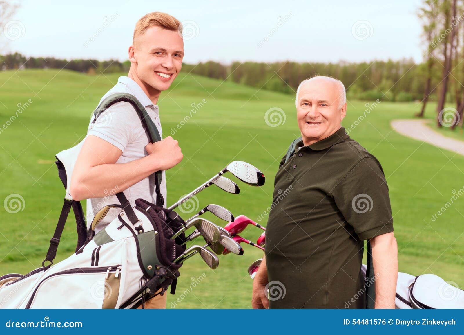 Giocatori di golf senior e giovani con attrezzatura